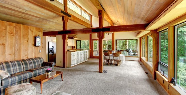 Large living room in a log cabin with large windows facing the nature