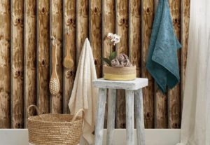 Log cabin wallpaper with a white stool in front and a pair of towels hanging from wall hooks