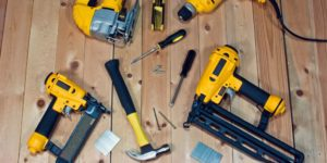 Power tools and manual hand tools scattered across a floor