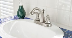 Spotlessly clean brushed nickel faucet mounted on a white sink