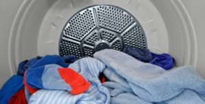 Clothes dryer drum half full of dried clothes