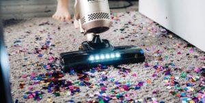 Vacuum cleaner sucking away confetti on a carpet