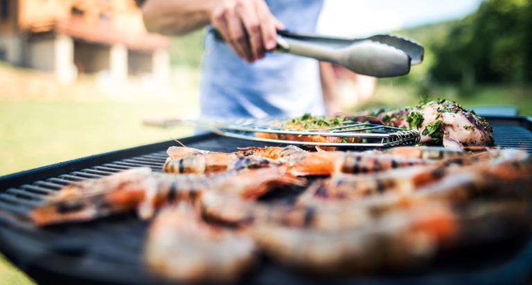 Man using tongs to turn food over on a grill