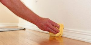 Male cleaning dirty baseboards inside a house