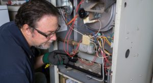 Technician inspecting a gas furnace up close
