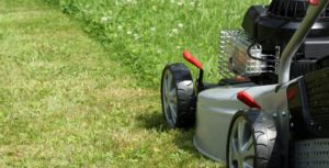 Mowing the lawn with a gas powered lawn mower