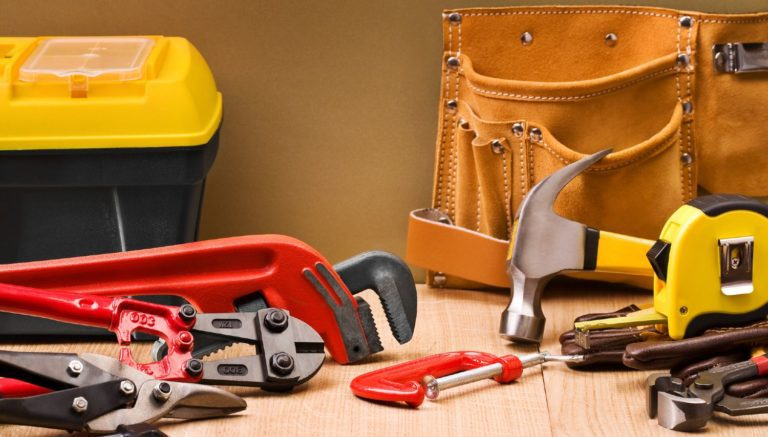 Tools scattered across a table with a tool box and a tool belt in the background