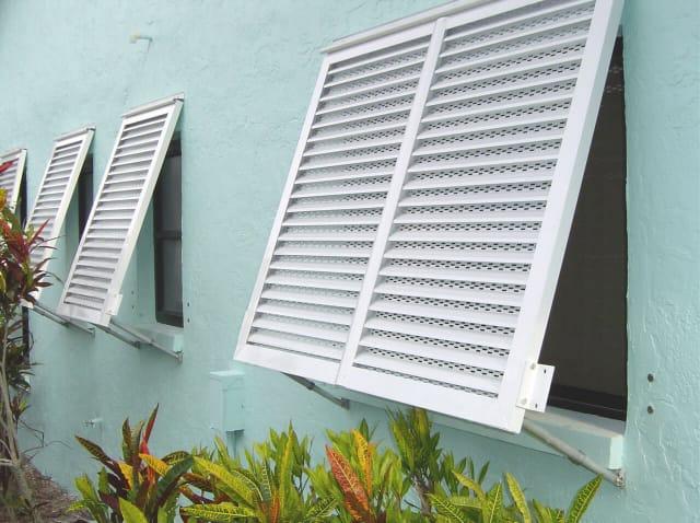 Hurricane Shutters Florida white Bahama shutters installed on a light blue building