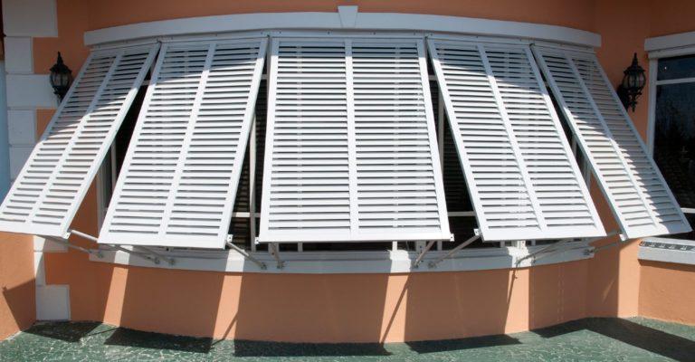 White Bahama shutters on an orange building