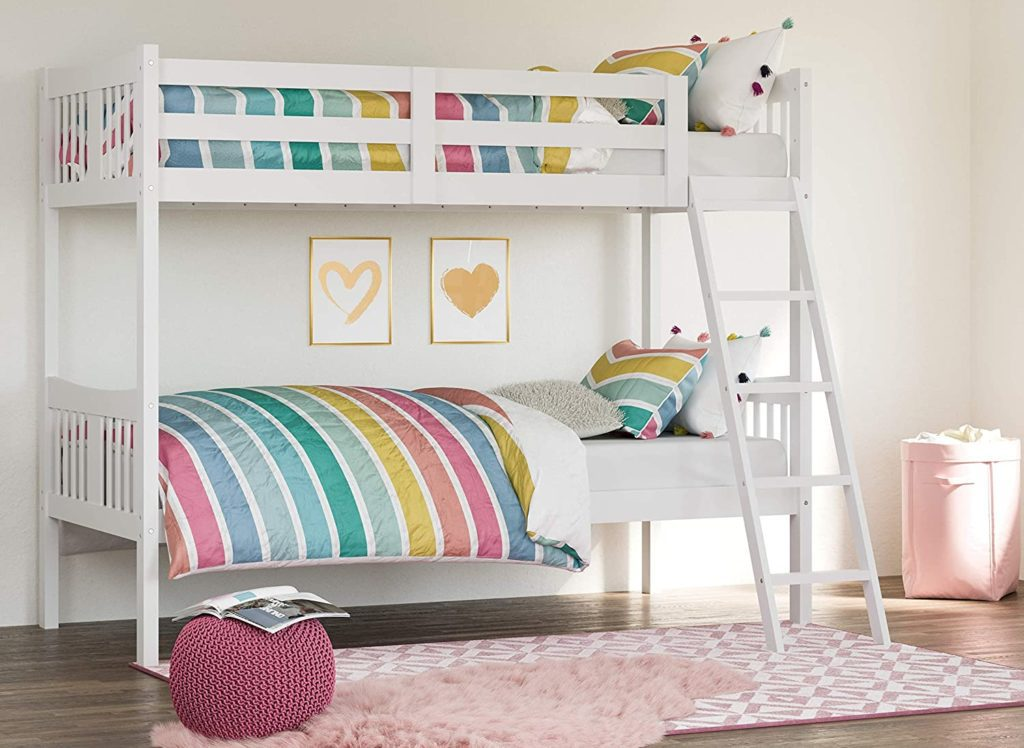 Bunk bed with a white wooden frame and rainbow colored bed linen in a bright room