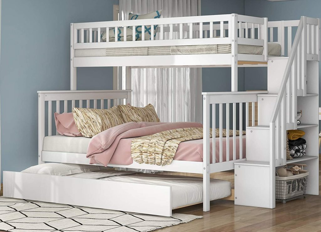 White wooden bunk bed with a trundle and a storage shelf staircase