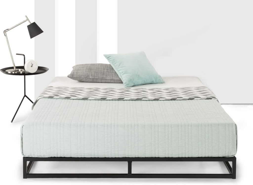 Black minimalistic metal platform bed frame with a black nightstand and a black lamp in a bright room