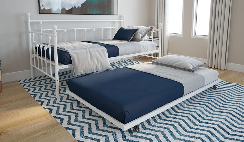 Trundle bed with a white metal frame and blue-gray bed linen