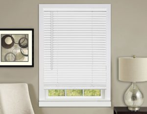 White blinds covering a window on a beige wall