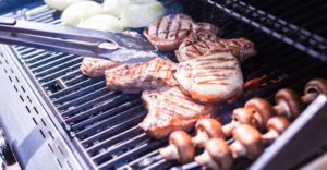 Cooking onions, mushrooms and pork chops on a gas grill