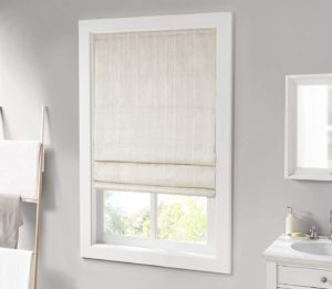 Light shades partially covering a window on a gray wall
