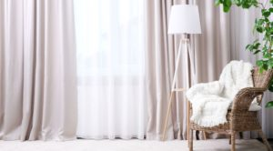 Oversized curtains in a beige fabric with an extra semi-transparent curtain underneath