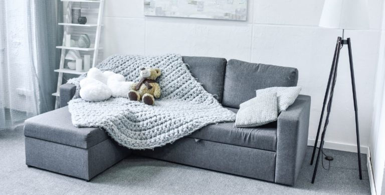 Gray sleeper sofa in a nicely decorated living room with gray carpet