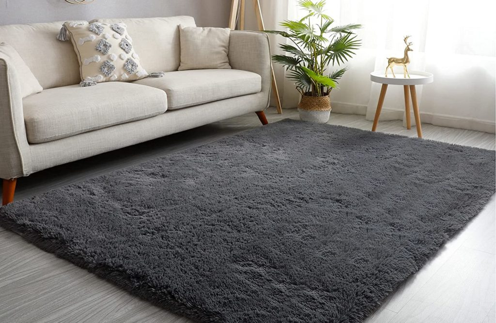 Soft cozy dark gray area rug in front of a beige sofa in a living room