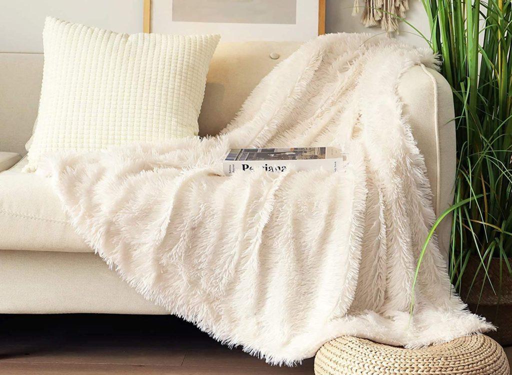 Soft white throw blanket on a white sofa